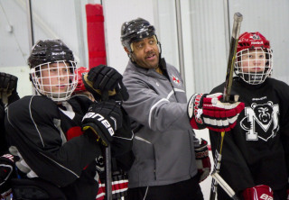 Former NHL player Graeme Townshend talks to members of the Maine Hockey Academy during practice at t