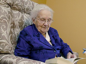 old_lady_sitting_in_a_chair_reading_a_book