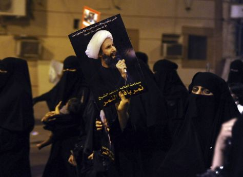 A protester holds up a picture of Sheikh Nimr al-Nimr during a rally at the coastal town of Qatif, against the cleric's arrest