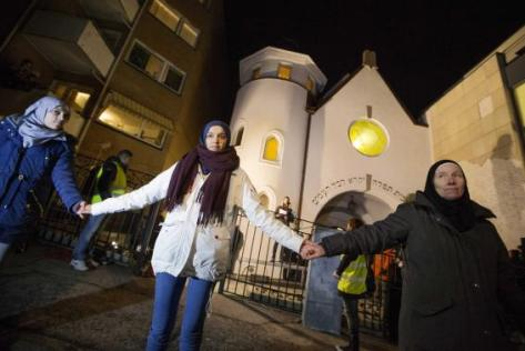 Muslim women join hands to form a human shield as they stand outside a synagogue in Oslo