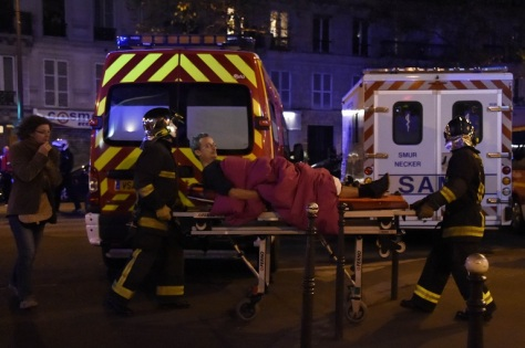Rescuers workers evacuate a man on a stretcher near the Bataclan concert hall in central Paris, on November 13, 2015. A number of people were killed and others injured in a series of gun attacks across Paris, as well as explosions outside the national stadium where France was hosting Germany. AFP PHOTO / DOMINIQUE FAGET