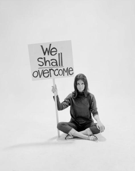 "Writer Gloria Steinem sitting cross-legged on floor w. sign ""We Shall Overcome"" re pop culture"