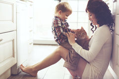 mother-child-playing-cat-her-baby-pet-floor-kitchen-home-49928308