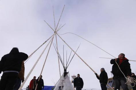 "Members of the Oglala Lakota tribe erect a tipi inside of the Oceti Sakowin camp as ""water protectors"" continue to demonstrate against plans to pass the Dakota Access pipeline near the Standing Rock Indian Reservation, near Cannon Ball, North Dakota, U.S., December 2, 2016. REUTERS/Lucas Jackson"