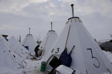 "A camper works on her tent inside of the Oceti Sakowin camp as ""water protectors"" continue to demonstrate against plans to pass the Dakota Access pipeline near the Standing Rock Indian Reservation, near Cannon Ball, North Dakota, U.S., December 2, 2016. REUTERS/Lucas Jackson"