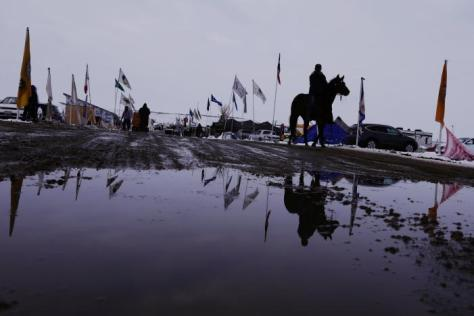 "A man rides a horse down a road inside of the Oceti Sakowin camp as ""water protectors"" continue to demonstrate against plans to pass the Dakota Access pipeline near the Standing Rock Indian Reservation, near Cannon Ball, North Dakota, U.S., December 2, 2016. REUTERS/Lucas Jackson"