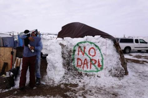 "Benji Buffalo (R) greets a friend to his campsite inside of the Oceti Sakowin camp as ""water protectors"" continue to demonstrate against plans to pass the Dakota Access pipeline near the Standing Rock Indian Reservation, near Cannon Ball, North Dakota, U.S., December 2, 2016. REUTERS/Lucas Jackson"