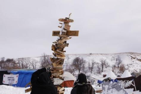 "Campers photograph a signpost with the names of various tribes on it inside of the Oceti Sakowin camp as ""water protectors"" continue to demonstrate against plans to pass the Dakota Access pipeline near the Standing Rock Indian Reservation, near Cannon Ball, North Dakota, U.S., December 2, 2016. REUTERS/Lucas Jackson"
