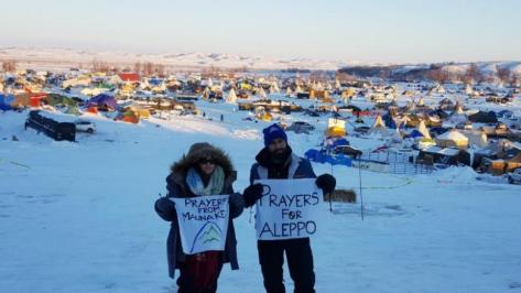 A couple of the remaining activists, hold up signs as they grapple with plunging temperatures that make conditions more difficult at the protest camp in Cannon Ball, North Dakota, December 14, 2016. Picture taken December 14, 2016. REUTERS/Valerie Volcovici