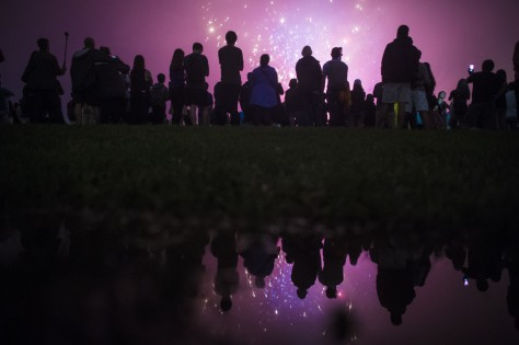 Patrons, reflected in a rain puddle, watch near the Washington Monument as the Independence Day fireworks go off on the National Mall on Monday, July 04. Getty