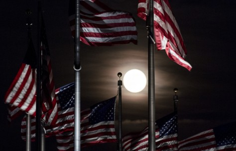 The full moon rises above the flags at the Washington Monument on Monday, June 20. June's full moon, also known as the Strawberry Moon, coincided with the summer solstice for the first time since the Summer of Love in 1967. Getty
