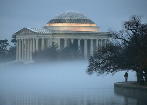 The Jefferson Memorial is surrounded in fog as a man rides a bicycle along the Tidal Basin, on November 30. Getty